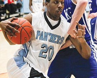 East's Terrell McClain (20) drives against Lake defender Alex Belinsky (21) during the Division I district semifinal Wednesday at Alliance High School. The Panthers' season ended in a 59-42 loss to the Blue Streaks.