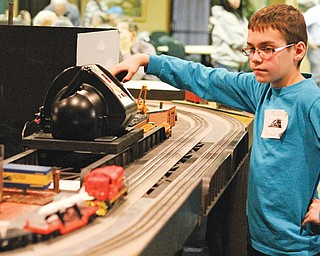 Brett Seybert, 10, of Fowler controls a model train on display during the Youngstown Model Railroad Association flea market at McMenamy's in Niles on Sunday. The youngster operated two model trains around a display built by the Western Reserve Model Railroad Club that depicts parts of Youngstown from days gone by.