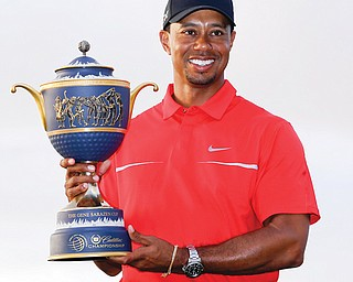 Tiger Woods holds the Gene Sarazen Cup after winning the PGA Cadillac Championship Sunday in Doral, Fla.