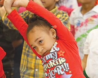 Isabella Torres, a kindergartner, stretches before participating in the strenuous exercise of the Radio Disney Dance Party at her school.