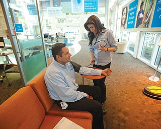 Yolanda Hormilla, a registered nurse working for Florida Blue, checks Jose Ballivian's blood pressure in the Sunrise, Fla., sales office. Some Americans could see their insurance costs double this year as the U.S. health-care overhaul expands coverage to millions of people.