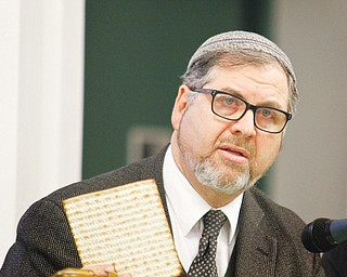 Rabbi Joseph Schonberger of Temple El Emeth in Liberty breaks the matzah during Wednesday night's Seder at St. Patrick Church in Youngstown. The event, sponsored by Generations of Faith, was a learning experience about the ritual meal.