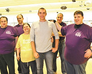 Tommy Warg, center, stands with some of the members of the Purple Cat men's bowling league recently at Camelot Lanes in Boardman. Photo by William D. Lewis | The Vindicator