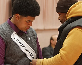 ROBERT  K.  YOSAY  | THE VINDICATOR --..Tavares Hodge  7th grader from Youngstown Christian school  gets his banner pinned on by his dad  Elliot as the BEE got underway ......The 80th  Youngstown Vindicator Spelling Bee was held at Kilcawley Center on YSU Campus  Saturday morning with  60 competitors from area schools.. ..(AP Photo/The Vindicator, Robert K. Yosay)