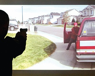 Hubbard Police Dept ptlm Brian Horne takes aim during a firearms training simualtion at the Police Dept Tuesday 3-19-13.