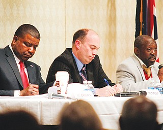 Youngstown Democratic mayoral candidates Jamael Tito Brown, left, and John McNally IV take notes as Matthew Smith speaks during their first debate Thursday night at Fellows Riverside Gardens' D.D. and Velma Davis Education & Visitor Center at Mill Creek MetroParks.