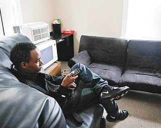 Jawan Johnson watches television in his Youngstown apartment. Johnson, 19, also has aged out of foster care and is living independently. He plans to attend Eastern Gateway Community College and YSU.