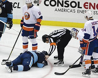 Pittsburgh Penguins center Sidney Crosby is helped by referee Ian Walsh after being hit in the face with a puck during the first period of a game against the New York Islanders in Pittsburgh on Saturday.