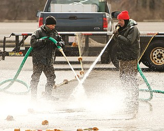 Ohio Department of Natural Resources workers Matt Wolfe, left, and Steve Moss didn't have too much fun in the cold Monday cleaning nets used this weekend to catch walleye eggs for hatching. Last month was colder with more snow than a typical March for the area, and the start of April wasn't any better.
