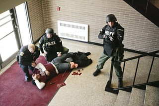 ROBERT K. YOSAY  | THE VINDICATOR..Tending to an injured student (Braxton Menendez a junior at BHS )- Ptl Paul Poulis and Sgt Mike Huges  - as Sgt Glen Riddle watches the staircaseBPD and area law enforcement had a mock drill of a shooter at Boardman High School - .. - -30-..
