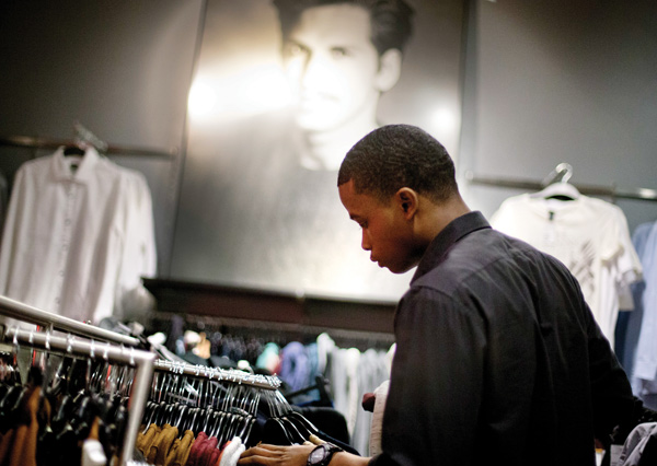 Dominic Plummer of Atlanta shops in an H&M store in Atlanta. Americans have grown more cautious and disciplined in handling their money since the financial crisis struck in 2008, a survey by Fidelity Investments suggests.