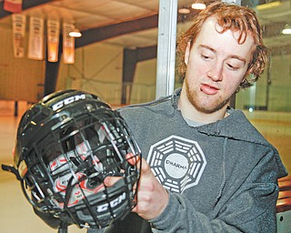 Youngstown Phantoms forward Cam Brown shows the caged helmet he wore in order to play in Saturday's game