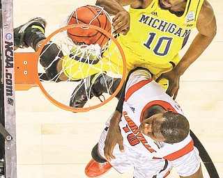 Michigan guard Tim Hardaway Jr. (10) dunks over Louisville center Gorgui Dieng (10) during the second half of the men's NCAA championship Monday in Atlanta. The No. 1-seeded Cardinals soared to an 82-76 victory over the No. 4-seeded Wolverines.