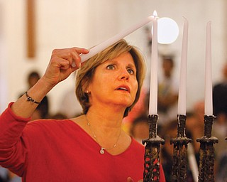 "Terri Anderson of Youngstown, a child of survivors of the Holocaust, lights the first candle during a ceremony at the 20th annual Yom Hashoah (Holocaust remembrance) on Thursday at the Mahoning County Courthouse. The theme was ""Never Again: Heeding the Warning Signs."""