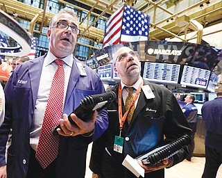 Traders Kenneth Polcari, left, and John Liotti work on the floor of the New York Stock Exchange. They were at work Friday.