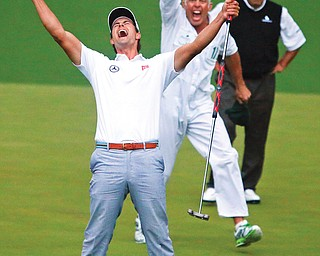Adam Scott and his caddie Steve Williams celebrate after Scott's putt dropped into the cup on the second hole of the playoff to win the Masters on Sunday in Augusta. Scott bested Argentine golfer Angel Cabrera, background, to become the first Australian to win the tournament.
