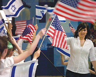 Talia Shlomi, a teacher at Akiva Academy, leads students during the opening ceremony Sunday of The Israel 65 Celebration at the Jewish Community Center in Youngstown. The event featured Israeli music, food, games and crafts.