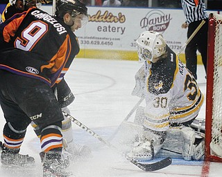 Austin Cangelosi (9) of the Youngstown Phantoms make an attempt on the goal which is defended by Green Bay goalie Tony Kujava (30) and defensman Jake Linhart (88) during Game 4 of their first-round USHL Clark Cup playoff series Sunday at the Covelli Centre in Youngstown. The Phantoms, who led the series 2-1 going into Sunday's contest, ousted the defending league champion Gamblers, 3-1, with Cam Brown netting the game-winning goal with 5:52 remaining in the third period and teammate Alexander Dahl adding an empty-net goal for insurance.