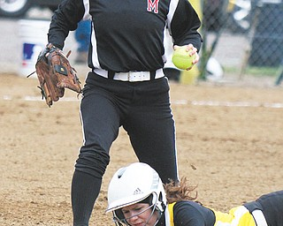 Bristol's Megan Adams dives back to first base ahead of a tag by Mathews Tabby Granelly (25) during a pick-off attempt in Thursday's softball game at Mathews High School. The Mustangs rallied to down the Panthers, 5-3, in 10 innings.