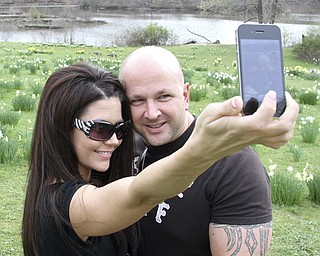 Shannon Kerr and Ken Hoover of Youngstown take a photo of themselves in Daffodil Meadow in Mill Creek Park. For generations, Valley residents have visited the popular spot as a rite of spring.