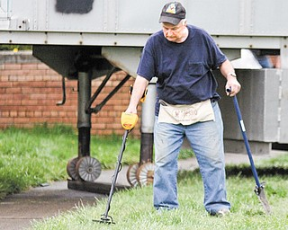 Dave Taylor of Warren uses his metal detector to help search for the Niles McKinley Class of 1964 time capsule.