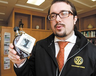 John Slanina, president of the Rocky Ridge Neighborhood Association, holds a bottle of Mill Creek pure maple syrup, gathered from sugar maples near Wick Recreation Area. The RRNA and Mill Creek MetroParks are selling the 300 bottles, with proceeds to be used for a playground in the recreation area and for neighborhood improvements.