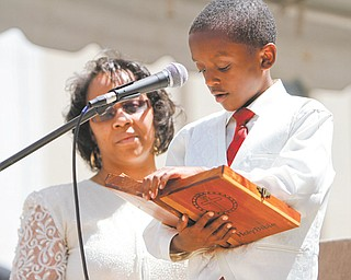 "Under the encouraging eyes of his mother, Hattie R. Hudson, 9-year-old Elisha J. Hudson reads his favorite passage from Psalm 23 that begins, ""The Lord is my shepherd,"" during National Day of Prayer on Thursday. Youngstown and Regional Prayer Team sponsored the event downtown with about 100 participating."