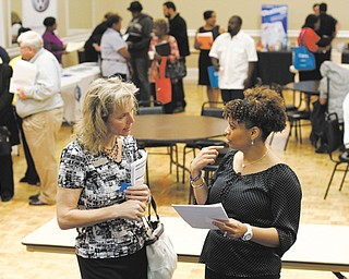 Donna Van Natten with The Enterprise Center, left, and Valoria Armstrong with Tennessee American Water Co. converse during a job fair Tuesday at the Urban League in Chattanooga, Tenn. The Labor Department reported Thursday that the number of Americans applying for unemployment aid fell last week to a seasonally adjusted 324,000 — the fewest since January 2008.