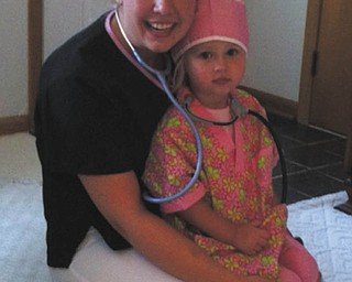 "Natalie Zwingler of Calcutta works in the NICU at Akron Children's Hospital in St. Elizabeth Health Center in Youngstown. This photo was sent in by her sister-in-law, Alyson Zwingler of Columbiana, who writes that Natalie ""is a very caring and compassionate nurse and aunt."" In the photo, Natalie gives a nursing outfit to Alyson's daughter Payton, now 5, for Payton's 3rd birthday. Alyson says, ""Payton wants to be just like Aunt Natalie when she grows up!"""
