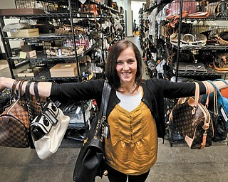 Sarah Davis, co-owner of Fashionphile.com, poses with her bags in a company warehouse in Carlsbad, Calif. The Internet company sells rare, vintage and discontinued previously owned bags and is facing the complicated task of dealing with new state regulations on Internet sale taxes.