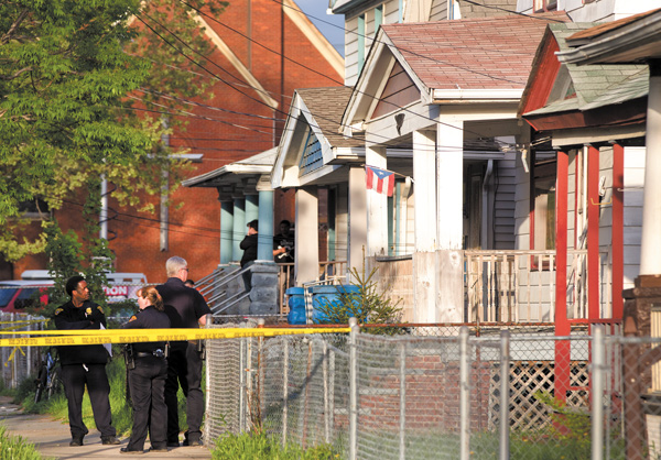 Cleveland police stand outside a home where they say Amanda Berry, Gina DeJesus and Michele Knight, who went missing separately about a decade ago, were found in the 2200 block of Seymour Avenue on Monday.