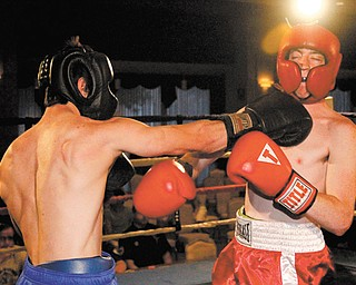 Ryan Patterson of Poland, left, hits Joshua Voland of Neshannock, Pa., on Monday night during the first round of the K.O. Drugs Boxing Tournament at St. Lucy's Palermo Center in Campbell.