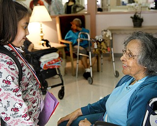 MADELYN P. HASTINGS | THE VINDICATOR   (L-R) Third grader in the afte rschool program at Martin Luther King Elementary, Amaryllis Rivera, gives a Mother's Day card to Metlean Singleton, resident at Danridge Nursing Home in Youngstown. The kids involved with the after school program presented the ladies of Danridge Mother's Day cards, songs and poems.
