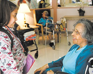 Amaryllis Rivera, a third-grader at Martin Luther King Elementary School, gives a Mother's Day card to Metlean Singleton, a resident at Danridge Burgundi Manor nursing home on Youngstown's East Side. The schoolchildren also sang songs and read poems Thursday.