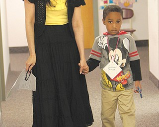 Sheila Palombo, who will be a kindergarten teacher at the new Austintown Elementary School, walks future kindergartner Quander Shouse through stations at kindergarten registration Thursday.