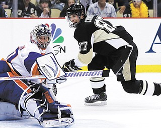 The Penguins' Sidney Crosby gets the puck past Islanders goalie Evgeni Nabokov for a second period goal in