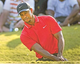 Tiger Woods hits onto the 15th green during the final round of The Players championship golf tournament Sunday at TPC Sawgrass in Ponte Vedra Beach, Fla.