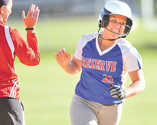 Western Reserve's April Lude smiles upon receiving a high fi ve from her coach Laura Amero as she rounds third base after hitting a two-run himer in the fourth inning of Monday's softball game against Columbiana in Columbiana. The Blue Devils extended their win streak in the ITCL Tier Two to 79 with a 10-5 victory over the Clippers.
