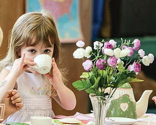 """Nina Hudock, who is in Jackie Jamieson's 3-year-old group at Serendipity Christian Preschool at Westminster Presbyterian Church in Boardman, holds up her """"pinky finger"""" as she sips her tea at a recent tea party. Manners and new tastes were the focus."""