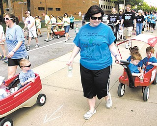 Kelly Robertson of New Middletown walks and pulls a wagon Sunday with her triplets, Mathew, Michael and Morgan, during the March of Dimes March for Babies that started at the WATTS Center at Youngstown State University. Robertson's children were born at 29 weeks.