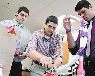 From left, Girard High School seniors Brandon Martuccio, Frank Rich and Alessandro Baschieri display their project, the Rube Goldberg, in their physics class that will be counted as college credit through Youngstown State University's College in High School program.