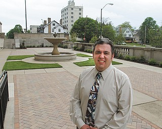 Chris Lewis, director of marketing and public relations at Stambaugh Auditorium, stands in the newly renovated formal garden space. Overgrown trees were removed to open up the area, available to rent for small events. Brick pavers were added. This summer, the space will be used for weekday concerts.