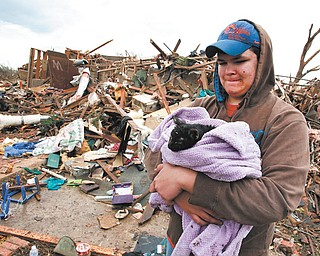 Austin Brock holds her cat, Tutti, after the animal was retrieved Tuesday from the rubble of Brock's home. The home was demolished Monday when a tornado moved through Moore, Okla.