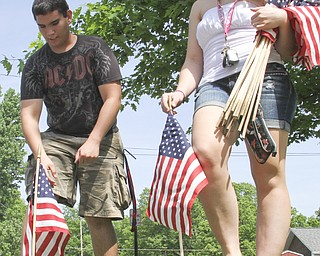 William D. Lewis\The Vindicator Austintown NHS members Ricky Ferry and Laura Wilson place flags along streets in Austintown.
