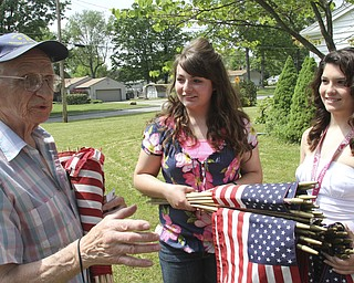 William D. Lewis\The Vindicator Meter Fromel, 85 and a Marine Corp vet passes out flags to Austintotwn Fitch NHS members Lynnette Seebacher,left, and LAura Wilson. The flags will be placed along 2 street sin Fromels Austintown neighborhood.