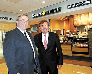 Rick Hodges, left, executive director of the Ohio Turnpike Commission, and Sam Covelli, right, owner/operator of Covelli Enterprises, stand in front of one of Covelli's Panera Bread cafes in the new Glacier Hills Service Plaza on the Ohio Turnpike in Springfield Township.