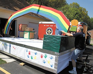 Duane Ward, a member of Westminster Presbyterian Church in Boardman, puts a rainbow in place on a float for Serendipity Christian Preschool at the church. Larry Hoff man is obscured by the rainbow.