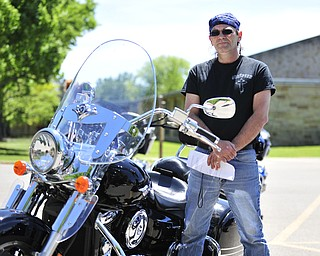 Brian Begg of Warren, Ohio stands beside his Kawasaki Vulcan Nomad motorcycle Saturday afternoon at Christ Episcopal Church in Warren.
