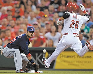 Cincinnati Reds' Xavier Paul (26) arrives at first with an infield hit as Cleveland Indians first baseman Nick Swisher awaits the throw in the fifth inning of a baseball game Tuesday in Cincinnati.