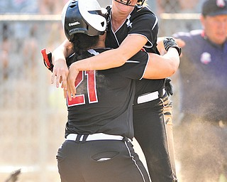 Mathews' Jacki Rhine (21) hugs teammate Jessica Marsico after Marsico scored the game-winning run in their Division IV regional softball semifinal against Cuyahoga Heights on Wednesday at Kent State University. The Mustangs downed the Redskins, 1-0.